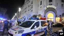 Une voiture de police est stationnée près du lieu où a eu lieu une attaque par camion qui a causé la mort de plusieurs dizaines personnes à Nice, France, 14 juillet 2016. (AP Photo / Christian Almiñana)