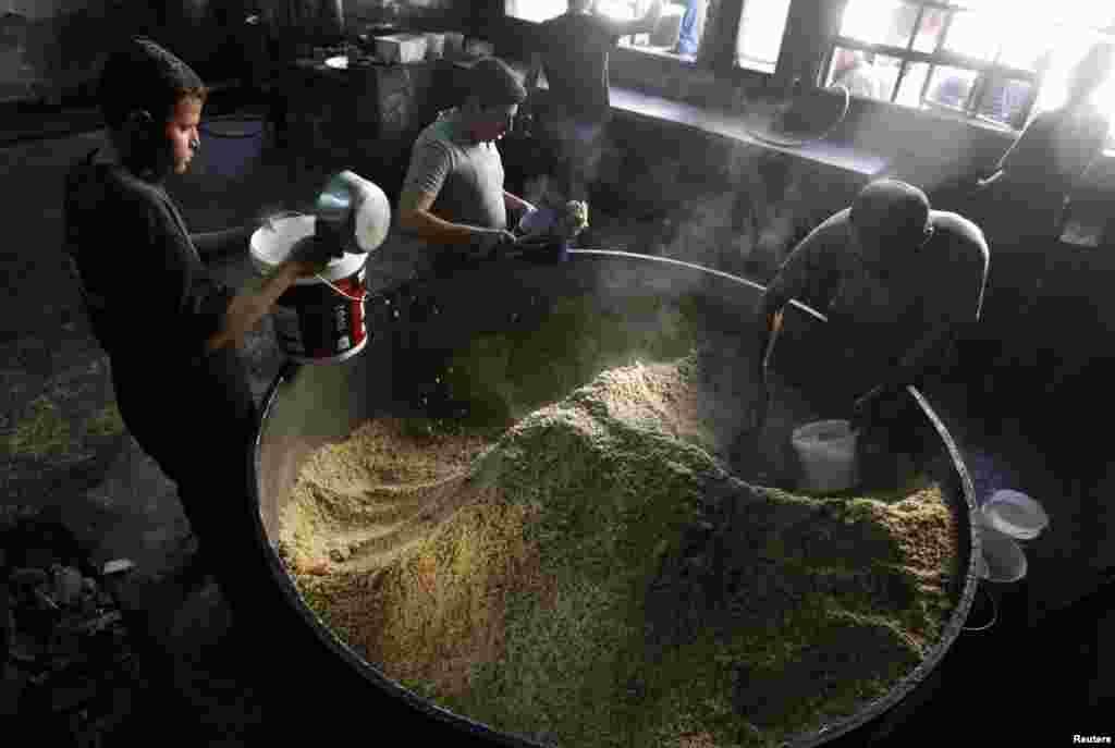 Para pekerja mempersiapkan makanan untuk dibagikan pada warga dan pengungsi di kota Raqqa, Suriah (7/10).