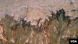 Gambar permukaan planet Mars yang dikirimkan oleh satelit pengamat NASA menunjukkan indikasi adanya air garam cair.