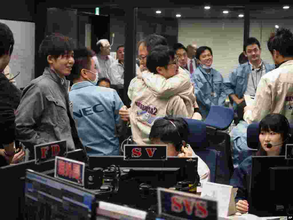 In this photo provided by the Japan Aerospace Exploration Agency, staff of the Hayabusa2 Project react as they confirm Hayabusa2 made a maneuver at the control room of the JAXA Institute of Space and Astronautical Science in Sagamihara, near Tokyo, Feb. 2