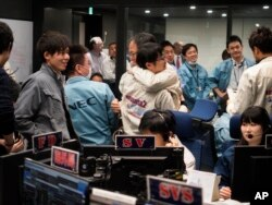 In this photo provided by the Japan Aerospace Exploration Agency, staff of the Hayabusa2 Project react as they confirm Hayabusa2 made a maneuver at the control room of the JAXA Institute of Space and Astronautical Science in Sagamihara, near Tokyo, Feb. 22, 2019.