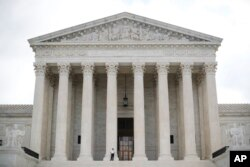 FILE - Police officer guards the main entrance to the Supreme Court in Washington.