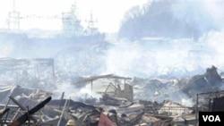 Tim penyelamat terus mencari korban di bawah asap di antara reruntuhan di Kesennuma, Jepang utara (14/3).