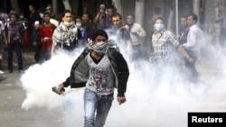 11月27日在开罗的解放广场,一位反对穆尔西的抗议者把警方释放的催泪瓦斯罐扔回去