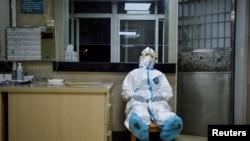 中國湖北省武漢市青山區一名身穿防護服的醫務人員在社區醫療站值夜班時稍事休息。(2020年2月9日)