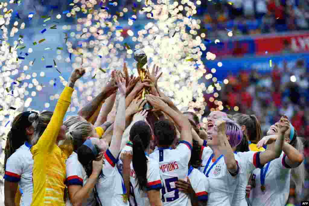USA's players celebrate with the trophy after the France 2019 Women's World Cup football final match between USA and the Netherlands, July 7, 2019, at the Lyon Stadium in Lyon, central-eastern France.
