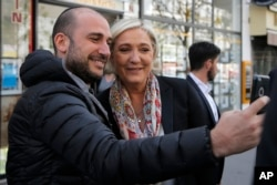 French far-right leader and candidate for the 2017 presidential election Marine Le Pen poses for a selfie after getting a haircut in Paris, April 24, 2017.