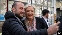 ຜູ້ນຳຝຣັ່ງ ຫົວນິຍົມຂວາຈັດ ແລະຜູ້ລົງສະໝັກປະທານາທິບໍດີ ປີ 2017 ທ່ານນາງ Marine Le Pen ຖ່າຍຮູບ selfie ໃນ Paris, 24 ເມສາ, 2017.