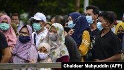 Orang-orang mengantri untuk memasuki Museum Tsunami - yang didedikasikan untuk para korban tsunami 2004 yang menewaskan sedikitnya 170 ribu orang di Indonesia dan ribuan lainnya di negara tetangga, Banda Aceh pada 2 Januari 2021. (Foto: AFP/Cha