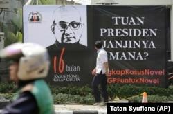 Seorang pria melihat poster di depan kantor KPK menyambut kembalinya penyidik Novel Baswedan, 27 Agustus 2018. Masyarakat mendesak Presiden Jokowi untuk membentuk tim pencari fakta dalam menyelesaikan kasus itu saat Novel kembali bekerja 16 bulan setelah
