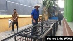 Chris Wilson, seorang ahli buaya asal Australia mempersiapkan perangkap sangkar besi yang akan digunakan untuk menangkap buaya berkalung ban di sungai Palu. (Foto: VOA/Yoanes Litha)