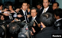 FILE - Cheng Yonghua, center, Chinese ambassador to Japan, is surrounded by the media as he speaks after meeting with Japan's Vice Minister for Foreign Affairs Akitaka Saiki at the Foreign Ministry in Tokyo, Nov. 25, 2013.