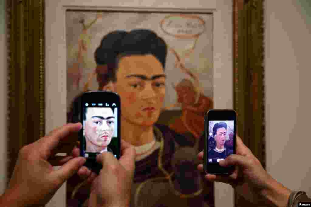 Khách tham quan chụp ảnh bức 'Tự họa với khỉ' của họa sĩ người Mexico Frida Kahlo (1907-1954) trong buổi giới thiệu triển lãm 'Frida Kahlo/Diego Rivera , Art in Fuson' tại bảo tàng Musee de l'Orangerie ở Paris, Pháp.
