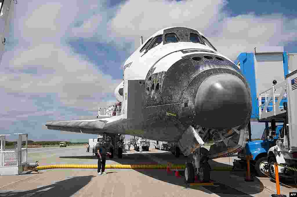 The landing convoy that will make space shuttle Discovery secure for towing to its processing hangar begins to pull up around the spacecraft at Kennedy Space Center in Florida, March 9, 2011. (NASA)