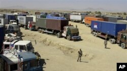 Pakistani border guards stand alert at a terminal of Afghanistan-bound NATO trucks parked at Pakistani border post of Chaman along Afghanistan on Wednesday, Oct. 6, 2010.