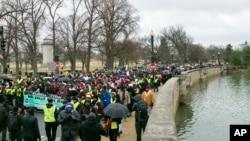 Activistas en pro de los derechos civiles marchan en honor del reverendo Martin Luther King Jr. el sábado 14 de enero de 2017 en Washington.