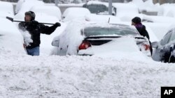 Workers at a Bloomington, Minnesota auto dealership remove snow left by a storm crawling east from the Dakotas and Minnesota toward Chicago that could bring up to 10 inches of snow in some areas, March 5, 2013.