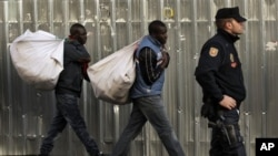 Immigrant street vendors in Spain walk along carrying their goods as police stand guard in Madrid, Spain