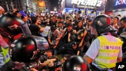 In this Nov. 26, 2014 file photo, police officers block pro-democracy protesters in the Mong Kok district during the Umbrella Movement in Hong Kong. (AP Photo/Kin Cheung, File)