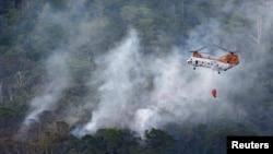 Sebuah helikopter militer AS berupaya memadamkan kebakaran di sekitar lokasi jatuhnya helikopter militer CH-46 di daerah latihan dekat Kamp Hansen di Okinawa, Jepang (5/8).