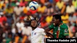 DR Congo's Dieumerci Mbokani, left, is challenged by Zambia's Kondwani Mtonga, right, Sunday, Jan. 18, 2015.