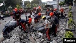 Regu penyelamat membersihkan reruntuhan yang mengubur kendaraan-kendaraan pasca gempa di kota Cebu, Filipina (15/10).