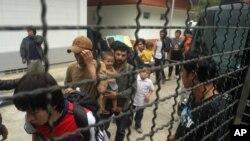 逃到泰国的维吾尔穆斯林在一辆警车旁站队(资料照片2014年3月15日)