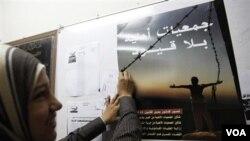 Seorang perempuan aktivis HAM di Kairo, memasang poster yang mengkampanyekan pemilu yang jujur dan adil, menjelang pemilu parlemen di Mesir hari ini.