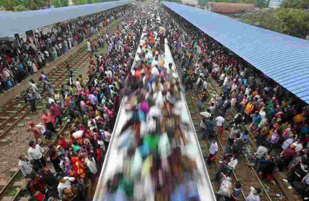 Muslims travel on the roof of a train to head home ahead of Eid al-Fitr as others wait at a railway station in Dhaka, August 8, 2013.