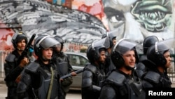 Riot police walk in front of graffiti depicting Bassem Mohsen, 20, who was killed in the 2011 Egypt uprising, along Mohamed Mahmoud street during the third anniversary of violent and deadly clashes near Tahrir Square in Cairo, Nov. 19, 2014.