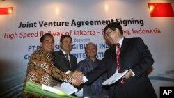 中方和印尼官员在签订中方承建印尼高铁的合同后握手(2015年10月16日)