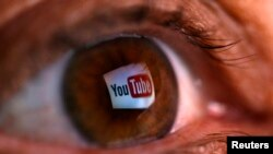 FILE - A reflection of YouTube's logo is seen in a person's eye.