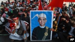 FILE - An image of deposed Myanmar President Win Myint is displayed at an anti-coup rally in Yangon, Myanmar, Feb. 20, 2021.
