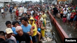 Typhoon victims line up for free rice at a businessman's warehouse in Tacloban city, which was battered by Typhoon Haiyan, in central Philippines. Nov. 12, 2013.