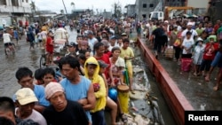 Typhoon victims queue for free rice at a businessman's warehouse in Tacloban city, which was battered by Typhoon Haiyan, in central Philippines. Nov. 12, 2013.