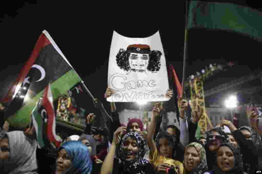 Women celebrate the revolution against Moammar Gadhafi's regime and ask for more women's rights, as they hols a banner depicting Moammar Gadhafi, Tripoli, Libya, Friday, Sept. 2, 2011. Rebel forces are advancing toward Moammar Gadhafi's hometown Sirte des