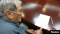 Esta foto muestra a Merrill Newman cuando estampa su huella digital en un documento preparado por Corea del Norte.