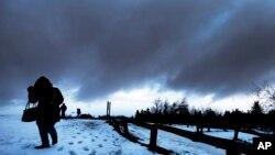 Una mujer camina en medio de una fuerte tormenta en la montaña Feldberg, cerca de Frankfurt, Alemania. Enero 3, 2017.