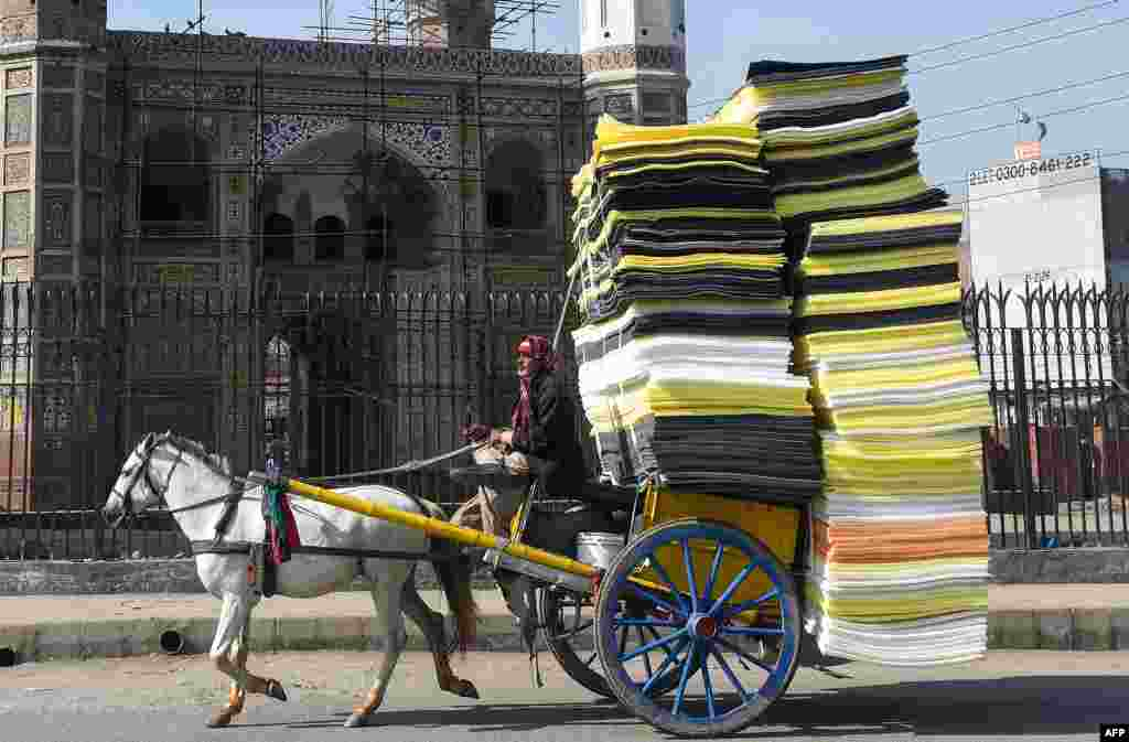 A man drives a horse-drawn carriage loaded with foam sheets on a street in Lahore, Pakistan, Jan. 29, 2019.