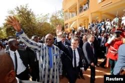 French President Emmanuel Macron and Burkina Faso's President Roch Marc Christian Kabore leave the Ouagadougou University, in Ouagadougou, Burkina Faso, Nov. 28, 2017.