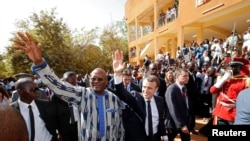 French President Emmanuel Macron and Burkina Faso's President Roch Marc Christian Kabore leave the Ouagadougou University, in Ouagadougou, Burkina Faso, Nov. 28, 2017.