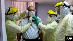 Di Panama, seorang pasien dengan kasus Covid-19 yang dikonfirmasi, dikelilingi oleh tim medis di unit perawatan intensif Rumah Sakit Paitilla di Panama City, 6 Mei 2020. (Foto: AFP)