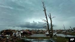 Awan badai di kejauhan di belakang rumah-rumah yang rusak karena tornado di Moore, Oklahoma (21/5). (AP/Charlie Riedel)