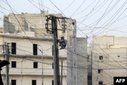 FILE - A man tries to fix electrical wires in the Salaheddin neighborhood of the northern Syrian city of Aleppo, Jan. 27, 2014.