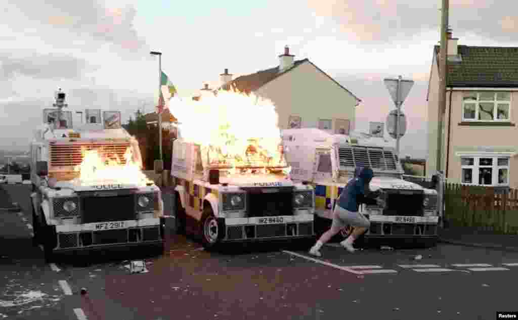 A person runs after throwing a petrol bomb at PSNI vehicles, after a security alert was upturned due to a suspicious package found in Creggan Heights, Derry, Northern Ireland in this still image obtained from a social media video.