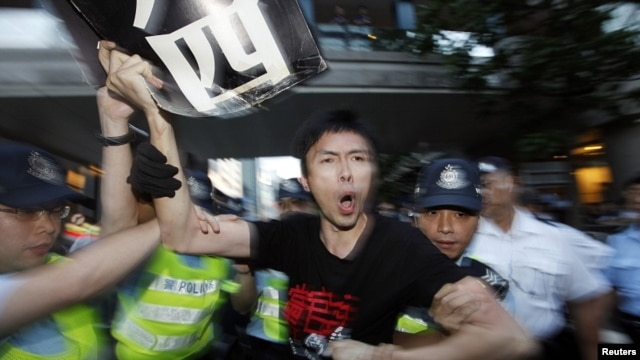 A pro-democracy demonstrator is arrested by the police after jumping the security fence, during a protest in front of the hotel where Chinese President Hu Jintao is staying, in Hong Kong June 30, 2012.