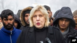 FILE - Surrounded by migrants, Dunja Mijatovic, the Council of Europe commissioner for human rights, addresses reporters at the Vucjak refugee camp outside Bihac, northwestern Bosnia, Dec. 3, 2019.