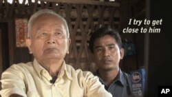 """Brother No. 2. Nuon Chea, sits with reporter Thet Sambath in this still from the movie """"Enemies of the People."""""""