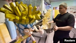 Yucel Bas prepares fries at Bas Frietjes frites stands in Sint Pieters Leeuw, Belgium, Dec. 4, 2014. (REUTERS/Yves Herman)