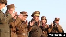 Ri Pyong Čol, visoki zvančnik nadgleda probu, ddrugi vojni zvaničnici aplaudiraju nakon lansiranja novog taktičkog vođenog projektila, 25. marta 2021, na fotografiji koju je dan kasnije objavila severnokorejska Korejska centralna novinska agencija (KCNA).
